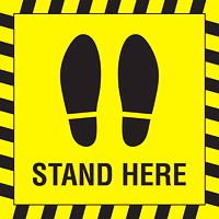 Autocollant de sol de distanciation sociale Sterling, anglais, Stand Here avec paire de pieds, noir sur fond jaune, 12po x 12po
